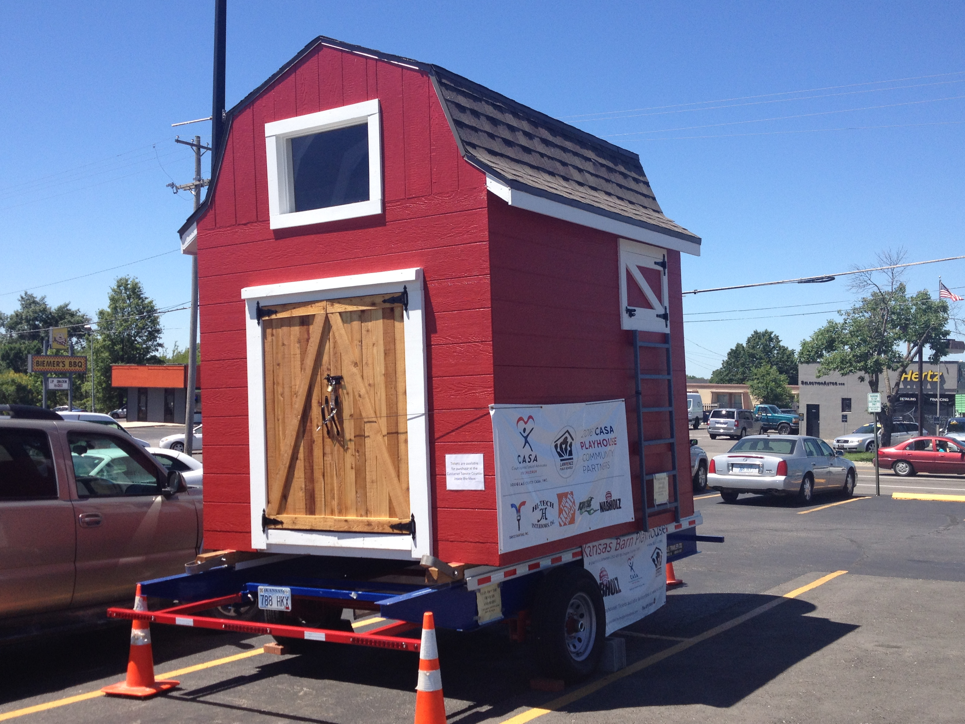 The 2016 Douglas County CASA playhouse is this cute barn, currently on display in the parking lot of The Merc (9th & Iowa) in Lawrence.  And you could win it with a single raffle ticket. (Photo by J. Schafer)