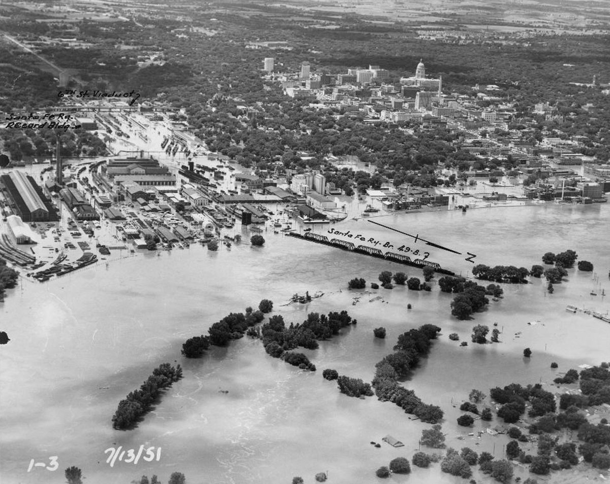 This aerial view looks southwest toward the Atchison, Topeka & Santa Fe Railway Eastern line, Eastern Division first district bridge, showing the flooding on the Kansas River in Topeka, Kansas. Date: July 13, 1951 (Photo Courtesy of Kansas Historical Society / kansasmemory.org)