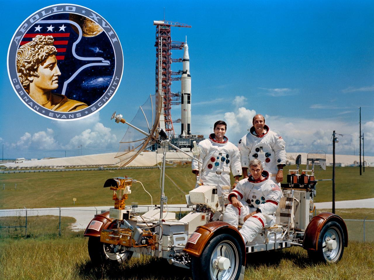 The prime crew members of the Apollo 17 lunar landing mission. They are Eugene A. Cernan (seated), commander; Ronald E. Evans (standing on right), command module pilot; and Harrison H. Schmitt, lunar module pilot. They are photographed with a Lunar Roving Vehicle (LRV) trainer. (Photo via NASA)
