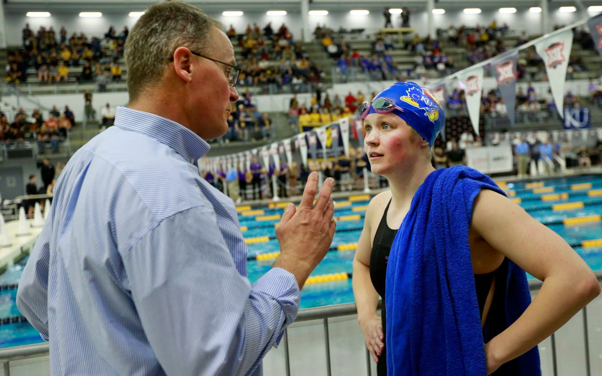 Coach and athlete.  KU swimming & diving coach Clark Campbell speaks with KU sophomore Kate Steward, who is now a two-time Big 12 champion in the 200-yard breaststroke.  (Photo by Laura Jacobsen, KU Athletics.)