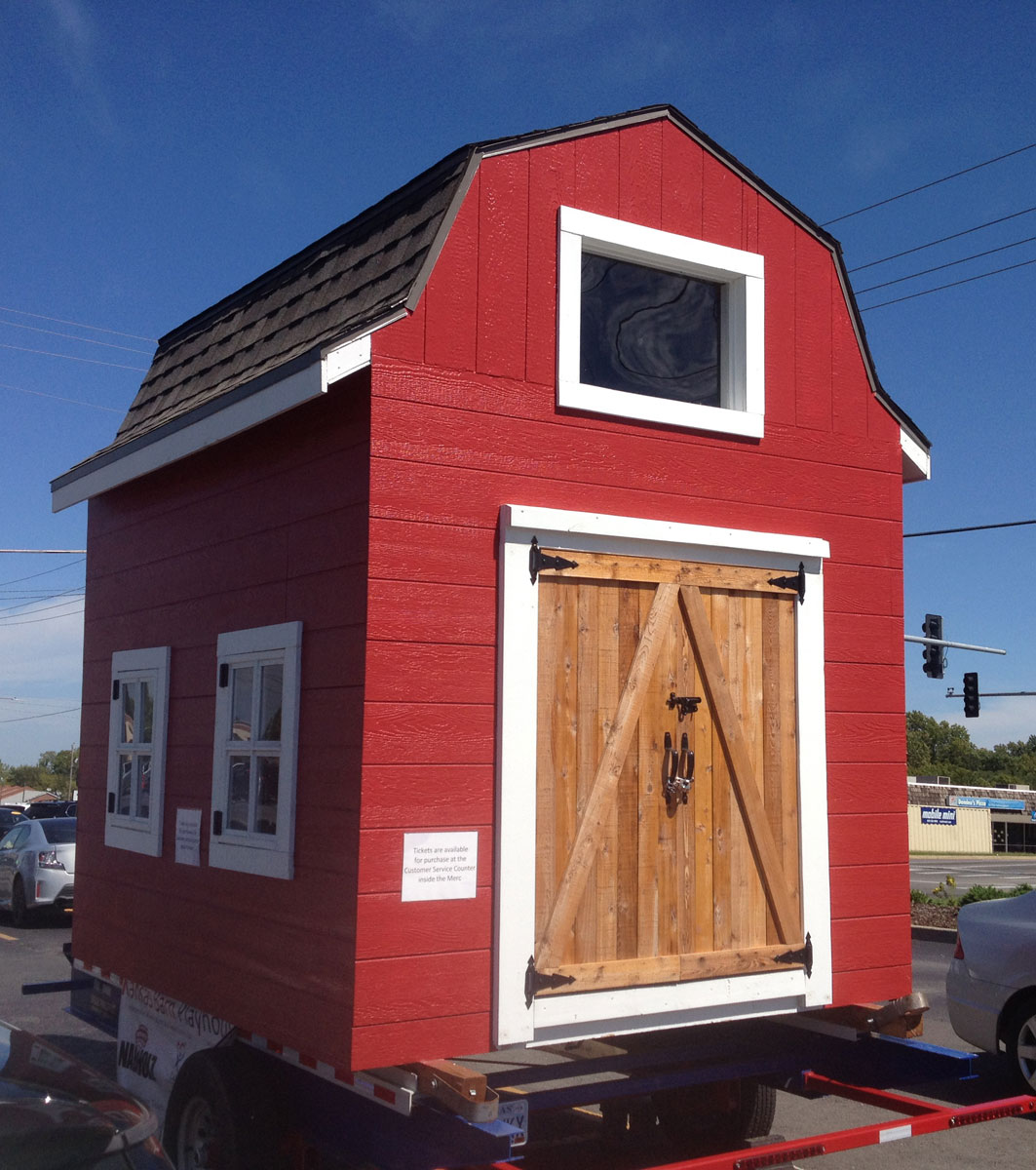 Front and left side of Douglas County CASA's playhouse barn, as seen in the parking lot of The Merc, 9th and Iowa Streets, in Lawrence. (Photo by J. Schafer)