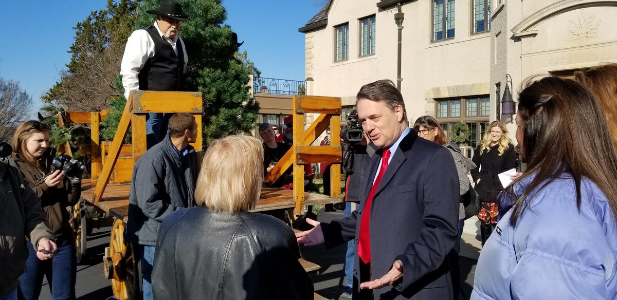 Kansas Governor Jeff Colyer (right) receives the 2018 Cedar Crest Christmas tree at the governor's mansion in Topeka. (Photo by Stephen Koranda)