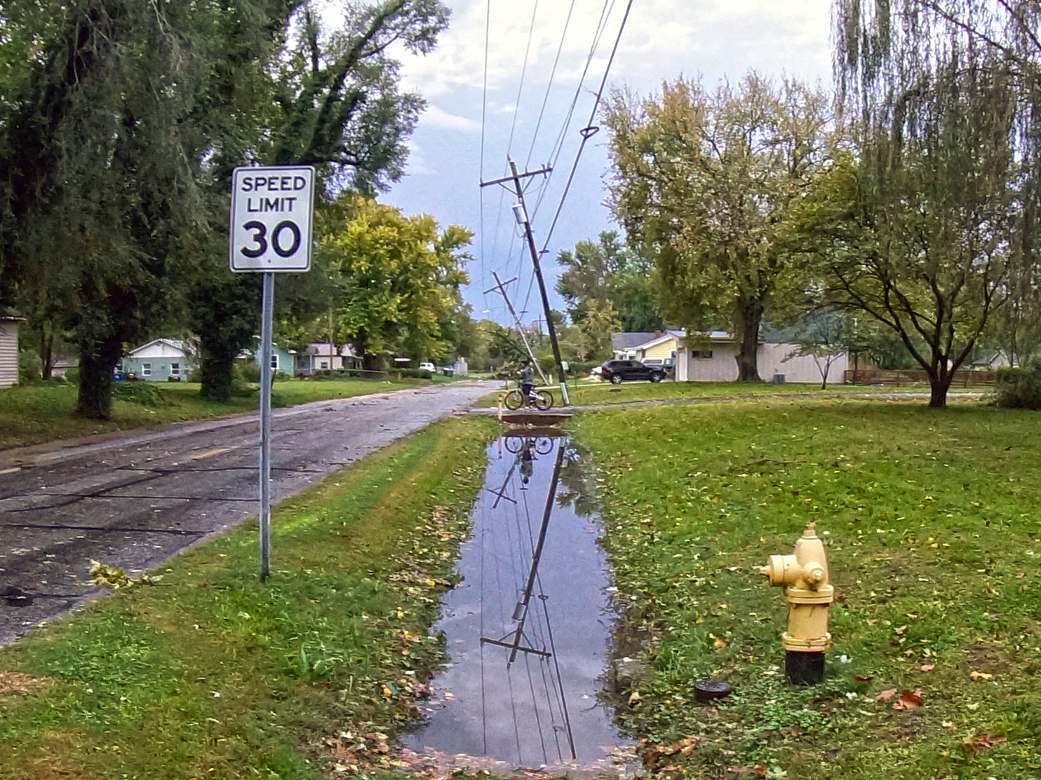 Utility poles lean toward the street after high winds blew through North Lawrence Saturday night. (Photo by Danny Mantyla)