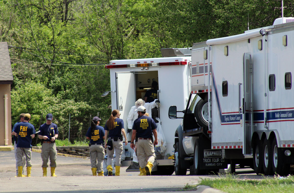 FBI agents process the scene of the Country Club Motel in Topeka, where a Saturday night shootout resulted in the wounding of three federal agents and a fire that totalled the motel. (Photo by J. Schafer)