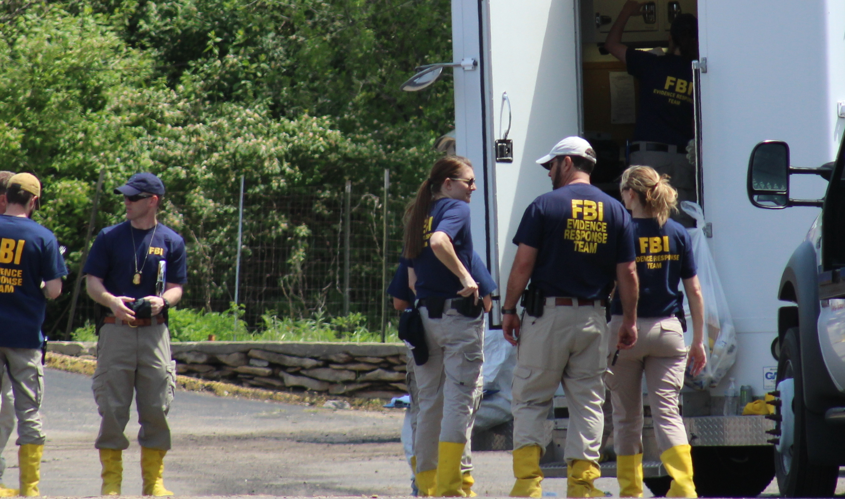 FBI crime scene investigators prepare to sift through the rubble of the burned-out Country Club Motel, where Saturday night's shootout and fire took place.  (Photo by J. Schafer)