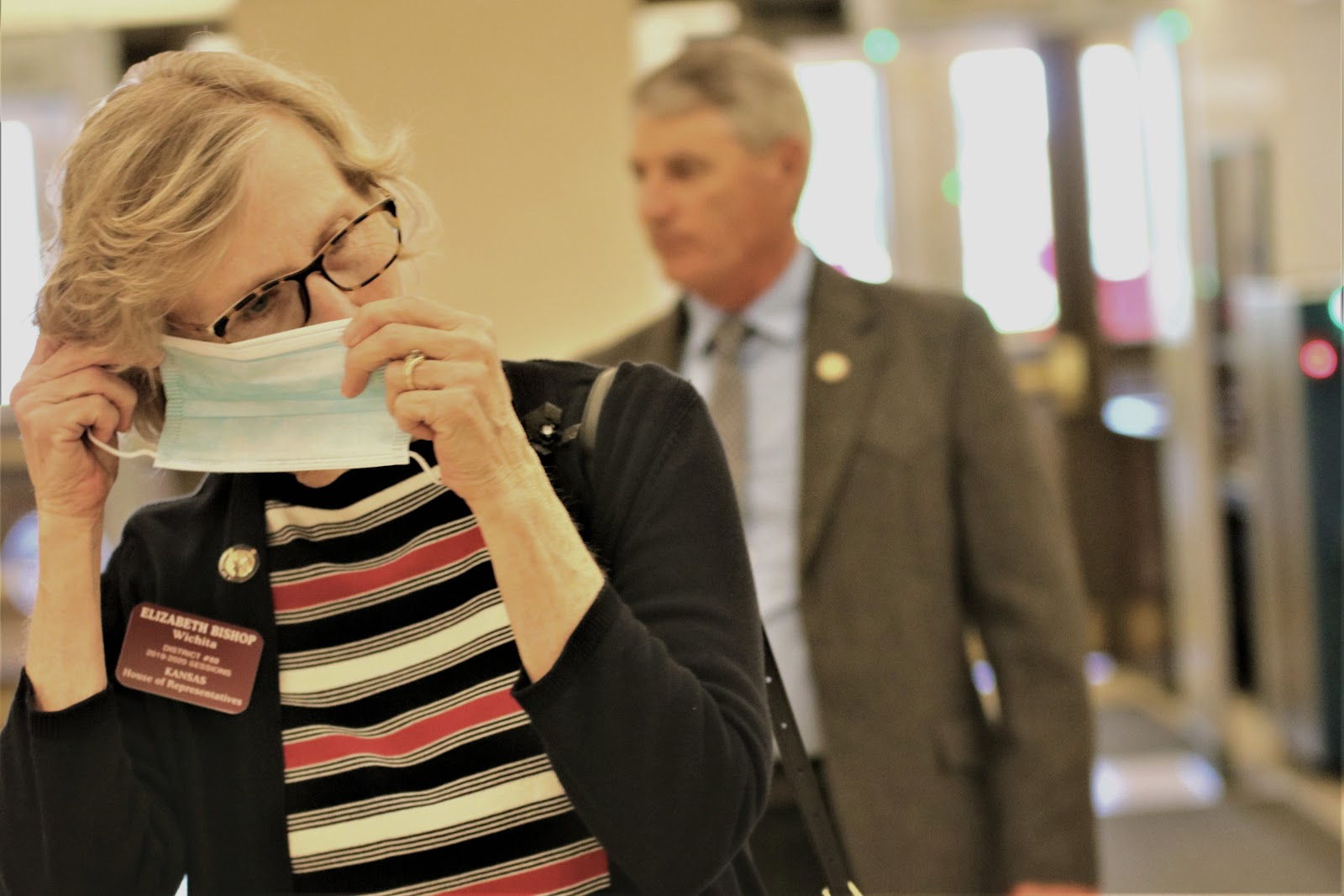 Wichita Democratic state Rep. Elizabeth Bishop puts on a mask as she enters the Statehouse on Thursday, the second day of the special session. (Photo by Jim McLean, Kansas News Service)