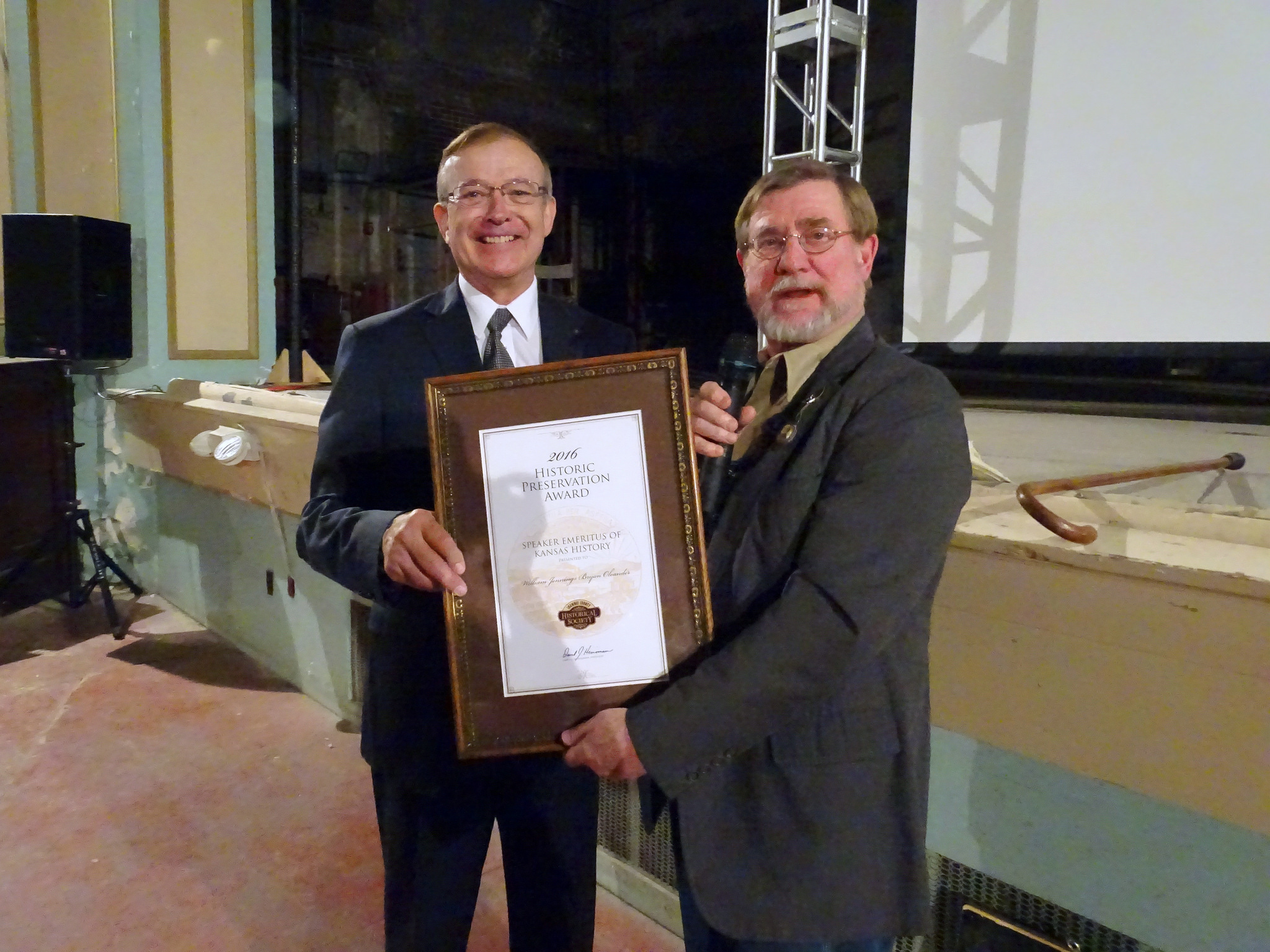 "Dave Heinemann (left), President of the Shawnee County Historical Society, presenting an award to KPR Commentator William Jennings Bryan Oleander, designating him ""Speaker Emeritus of Kansas History."" (Photo by Flint Hills Gal)"