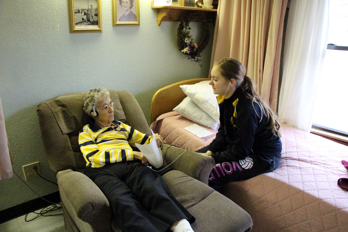 Brooke Beier, a student at Linn High School, helps Beverly Milburn with her music selection at Linn Community Nursing Home. Beier and other high school students volunteer with the program, which uses music to soothe people with Alzheimer's disease. (Photo by Marcy Oehmke, Linn High School)