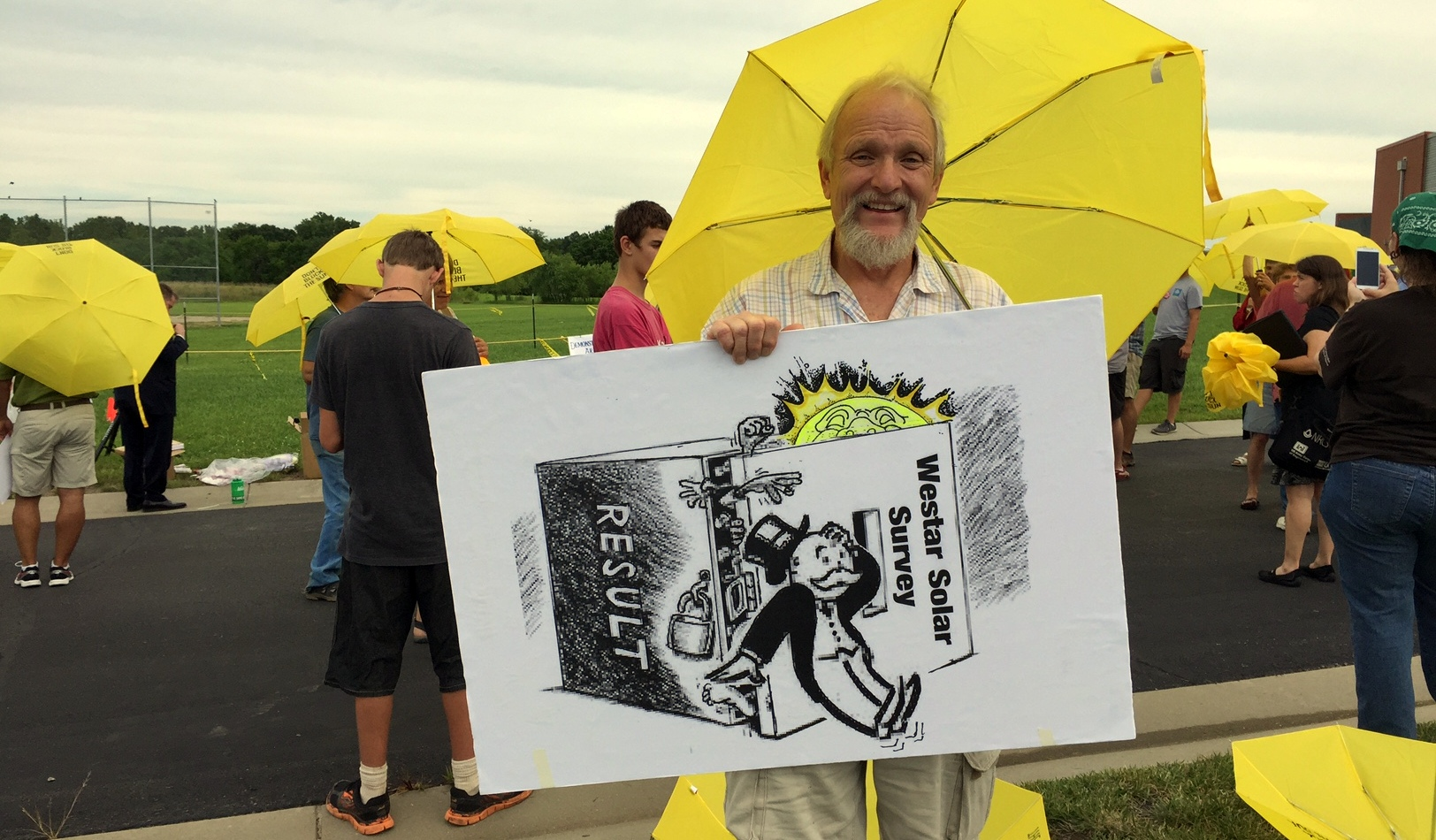 Bill Dorsett and other opponents of the Westar plan hold yellow umbrellas to show their support for solar power. (Photo by Stephen Koranda)