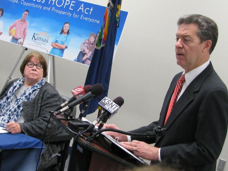 Kansas Department for Children and Families Secretary Phyllis Gilmore looks on as Governor Sam Brownback discusses a welfare reform measure that will take effect July 1.  (Photo by Dave Ranney, KHI News Service)