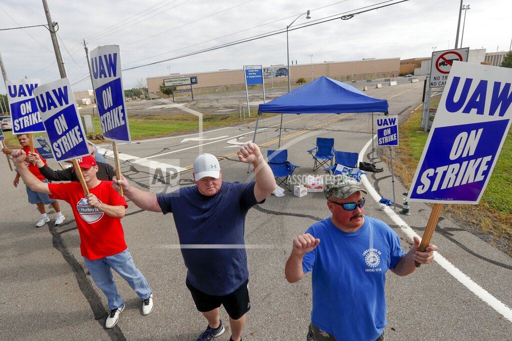 In this September 16, 2019, file photo, picketers carry signs at one of the gates outside the closed General Motors automobile assembly plant in Lordstown, Ohio.  Many from Lordstown, Ohio, and near Baltimore and Detroit are opposing a deal that could end a 37-day strike that crippled GM's U.S. production and cost the company an estimated $2 billion. (AP Photo / Keith Srakocic, File)