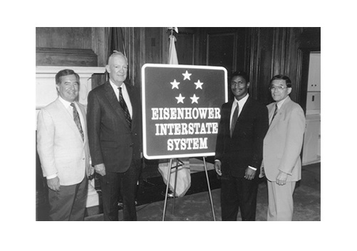 John Eisenhower and U.S. Department of Transportation officials unveil the Eisenhower Interstate System commemorative sign adopted in 1993. The five stars honor Eisenhower's service as General of the Army during World War II. (photo credit: U.S. Department of Transportation via commons.wikimedia.org)