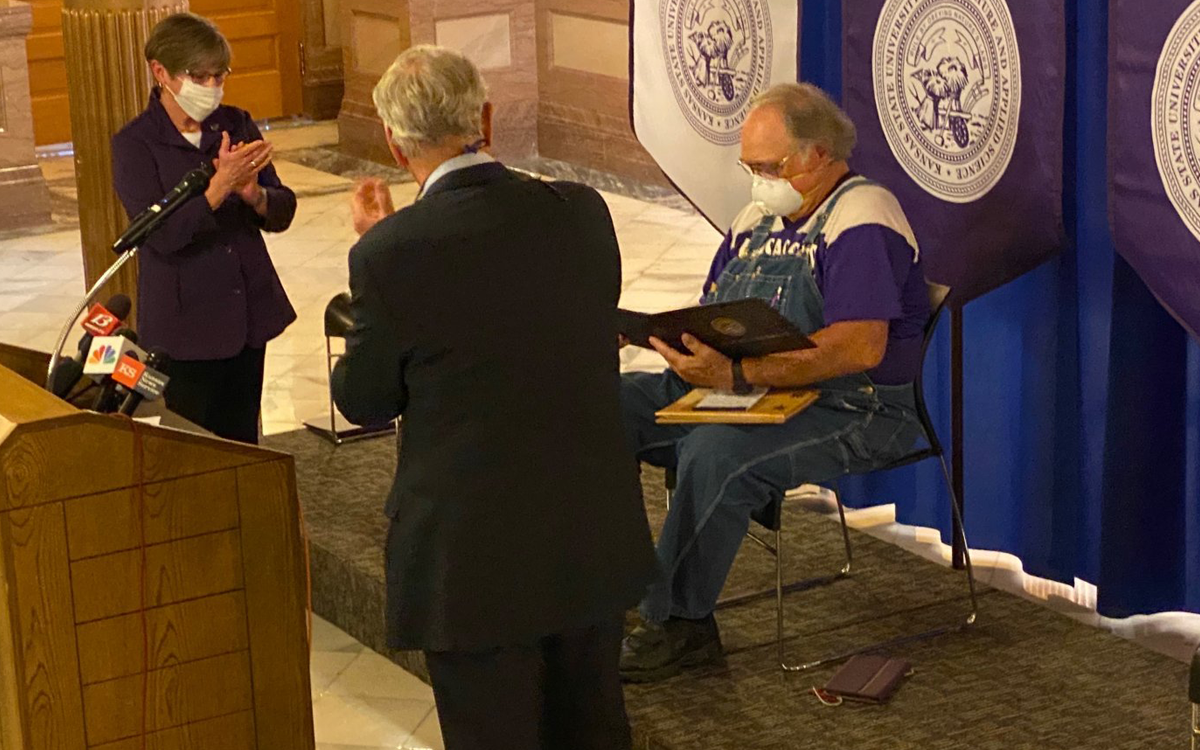 Governor Laura Kelly and K-State President Richard Myers conferred a degree upon retired Kansas farmer Dennis Ruhnke, of Troy, who sent an N95 mask to New York's governor.  Governor Kelly said Tuesday that Ruhnke shows the best in humanity and encapsulates what it means to be a Kansan. (Photo from governor's office.)