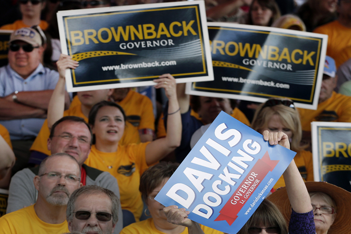 Volunteers with campaign signs during a debate between Sam Brownback and Paul Davis, at the Kansas State Fair in 2014. (Image credit: AP)