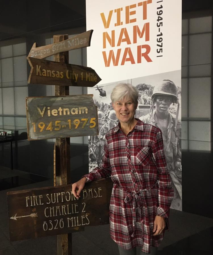 Kaye McIntyre and Vietnam signpost, Exhibit poster in background