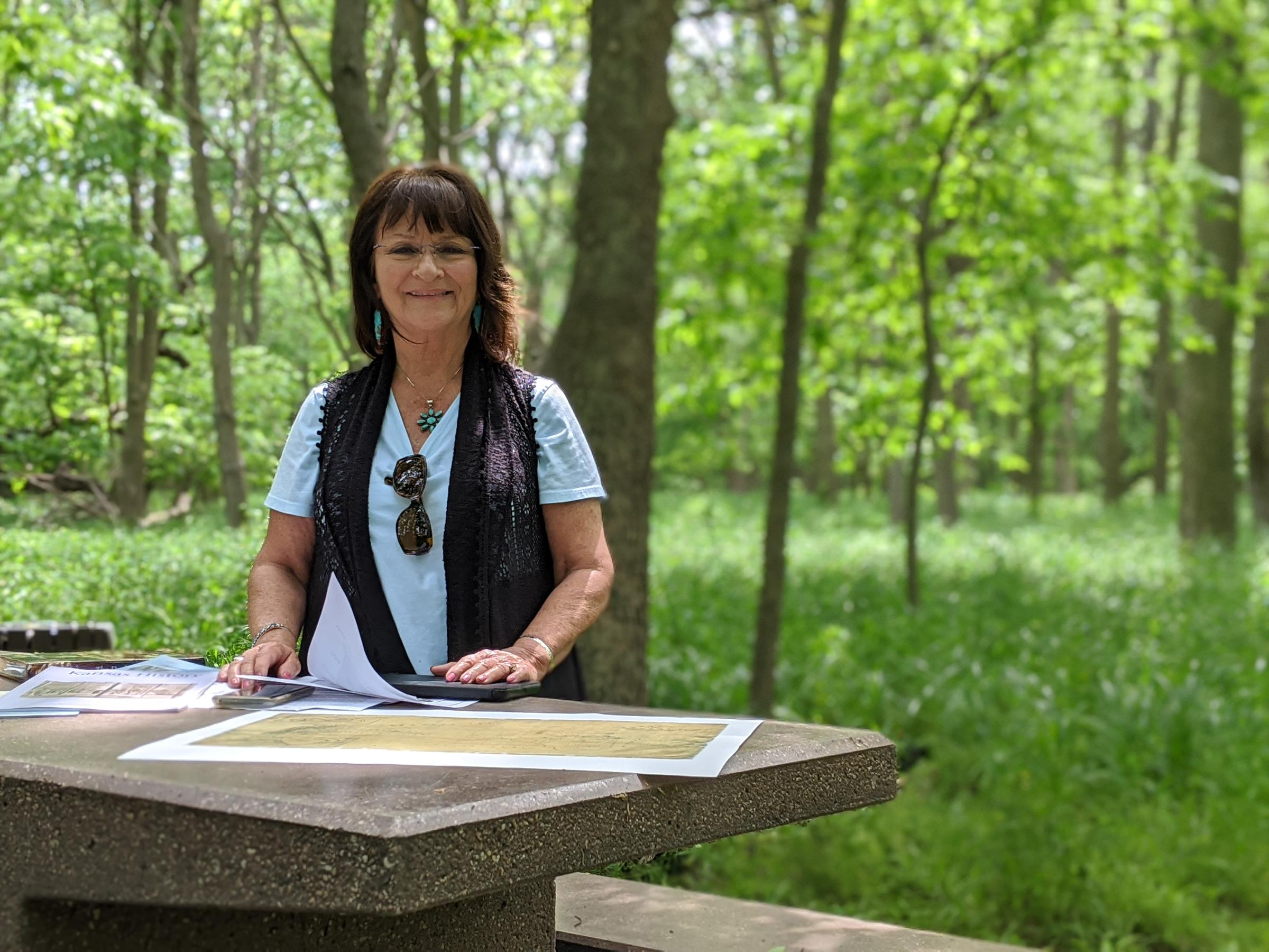 Pauline Sharp shows a map of Kanza land in the 1800s during a visit to Allegawaho Memorial Heritage Park. (Photo by Stephan Bisaha, Kansas News Service)