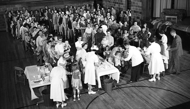 A crowd of people receives inactivated poliovirus vaccine (the Salk vaccine) in Protection, Kan.  The small southwest Kansas town became the first in the nation to be fully-immunized against polio.  Similar lines formed during the 1954 vaccine field trials. (Photo via March of Dimes Foundation)