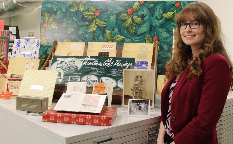 Hallmark Archives historian Samantha Bradbeer stands next to a display of early gift wrap samples.  (Laura Spencer / KCUR)
