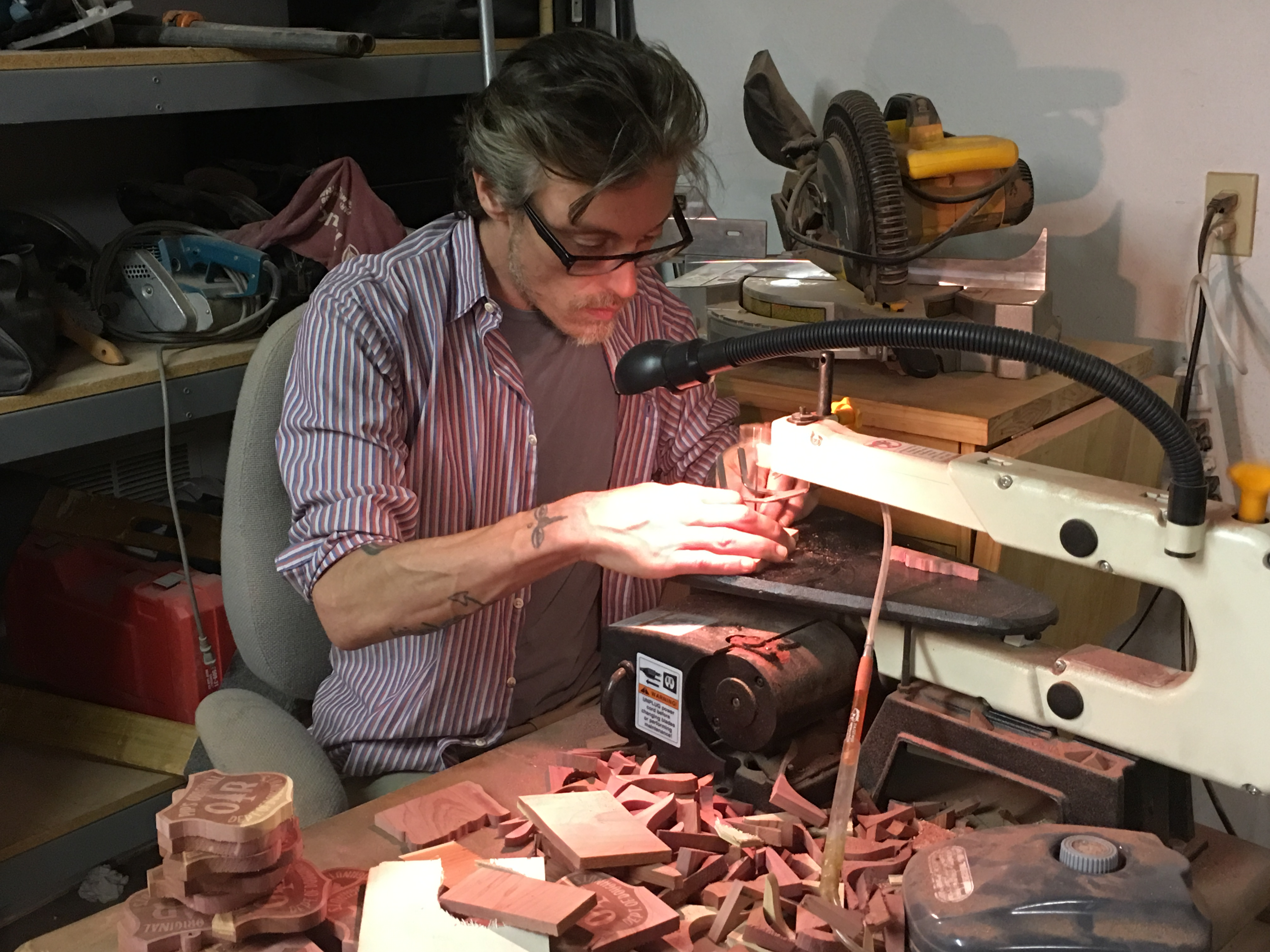 Lawrence resident Shine Adams founded Sun Cedar to help people down on their luck. He is pictured here using a scroll saw, one of the company's pieces of carpentry equipment. (Photo by Dan Margolies)