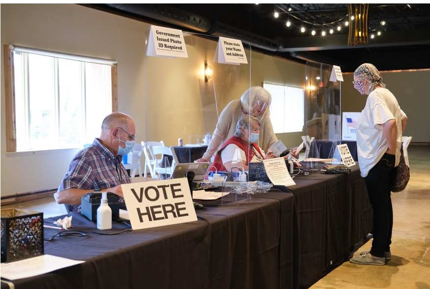 Poll workers sign-in voters during the August, 2020, primary in Wichita. Under a new Kansas election law, people can be criminally charged for appearing to impersonate an election official. That's prompted non-partisan groups to halt voter registration events while the law is challenged in court. (Photo by Brian Grimmett, Kansas News Service)