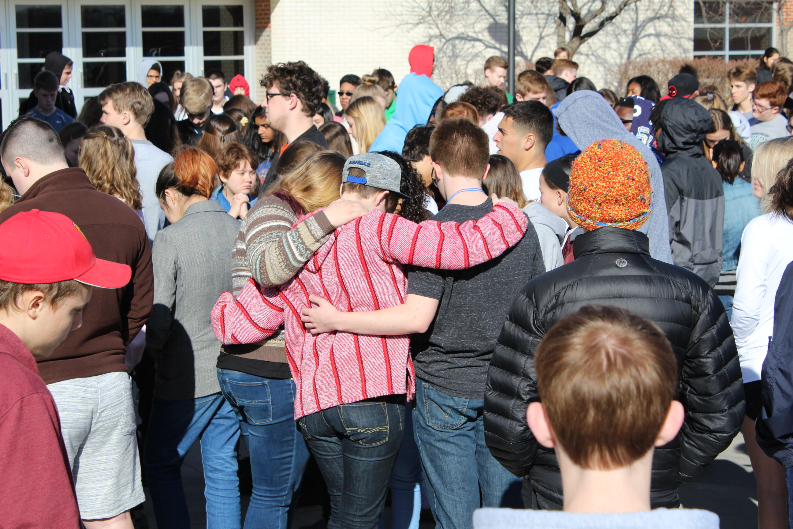 Several students embrace during the 17 minutes of silence observed at Lawrence's Free State High School. (Photo by J. Schafer)