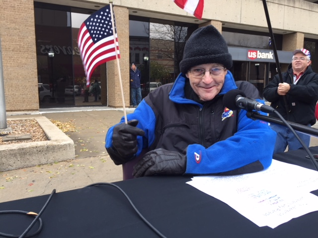 KLWN Radio broadcaster Hank Booth worked the public address system at 9th and Mass before and during Lawrence's Veterans Day parade.