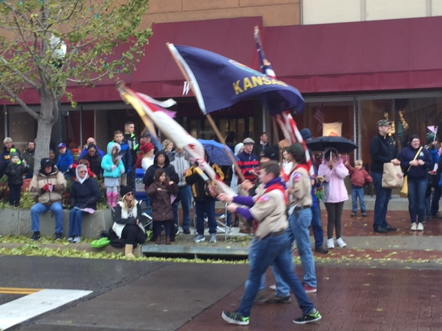 Boy Scouts carrying flags as they march past a crowd in front of Weaver's Department Store.