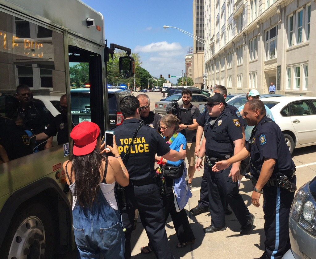 Protesters are loaded onto a bus by police. (Photo by Stephen Koranda)