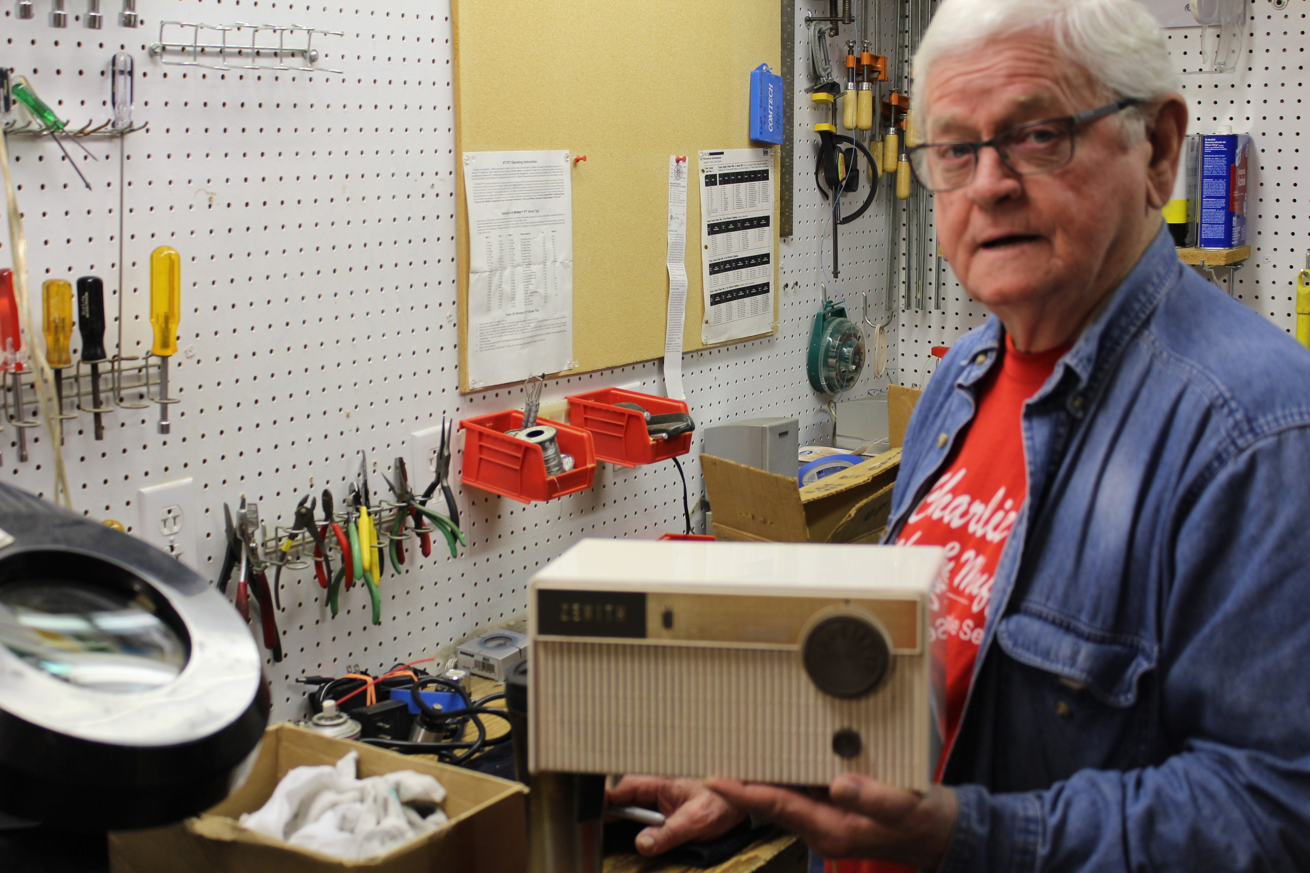 Lenexa resident Johnny Davis is another volunteer who helps restore audio equipment for Audio-Reader. In this photo, Davis works on an old Zenith table top radio. (Photo by J. Schafer)