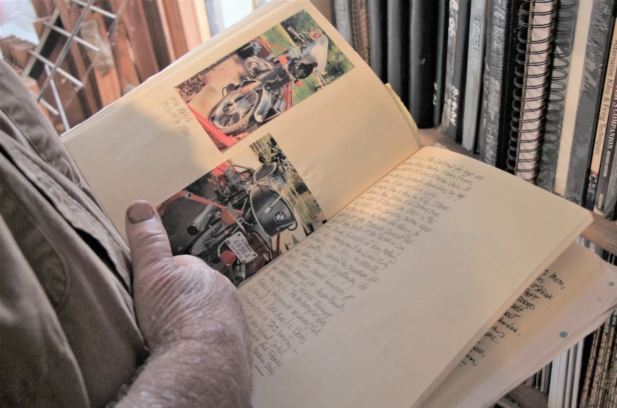 Letner, an artist and sculptor, flips through a journal with photos of his now-destroyed motorbike. He has chronicled his daily thoughts and experiences since the accident. (Photo by Celia Llopis-Jepsen, Kansas News Service)