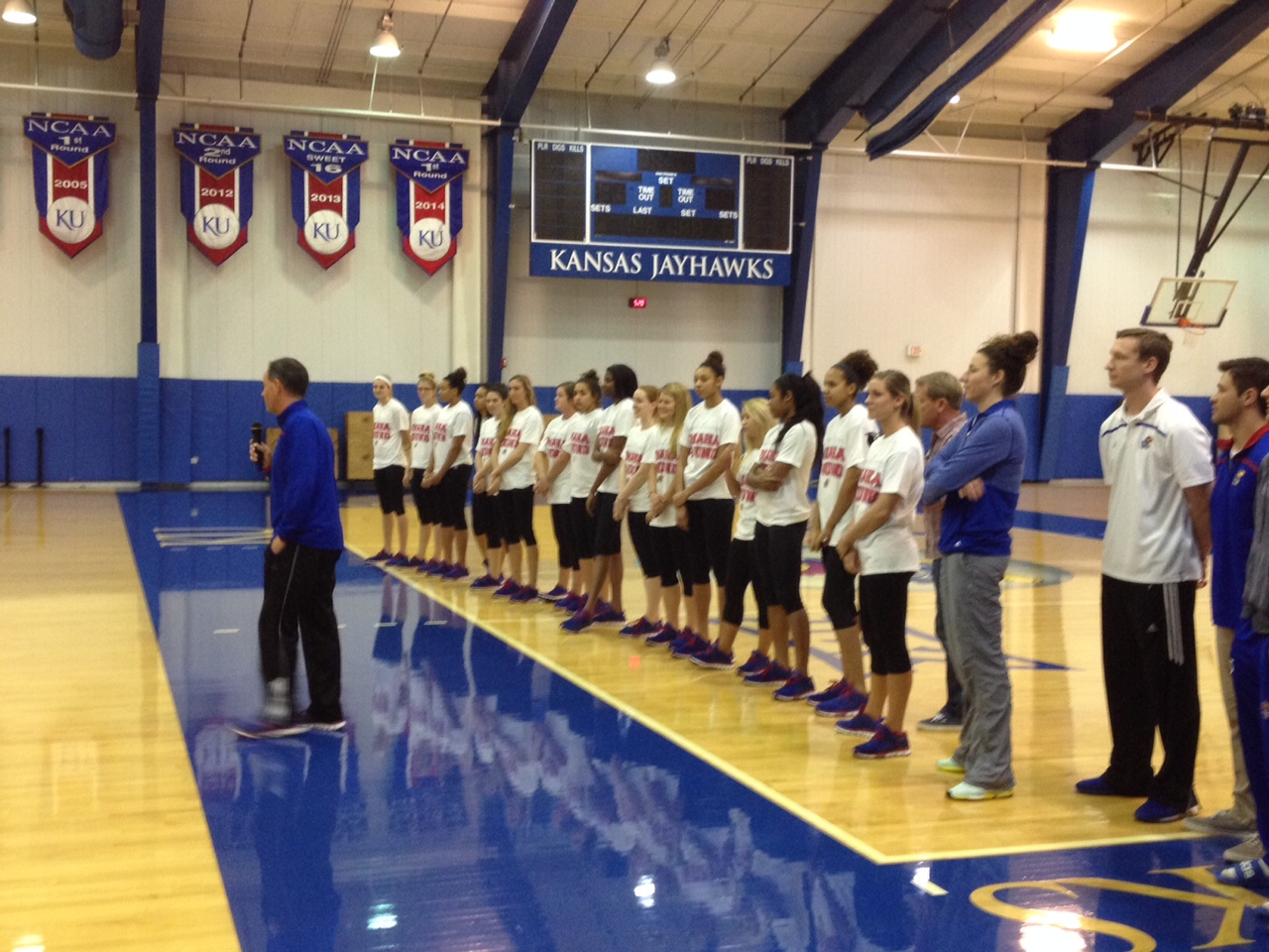 KU Volleyball Coach Ray Bechard and team members address the crowd at Horejsi Family Athletics Center, following weekend wins at NCAA tournament in San Diego. (Photo by J. Schafer)
