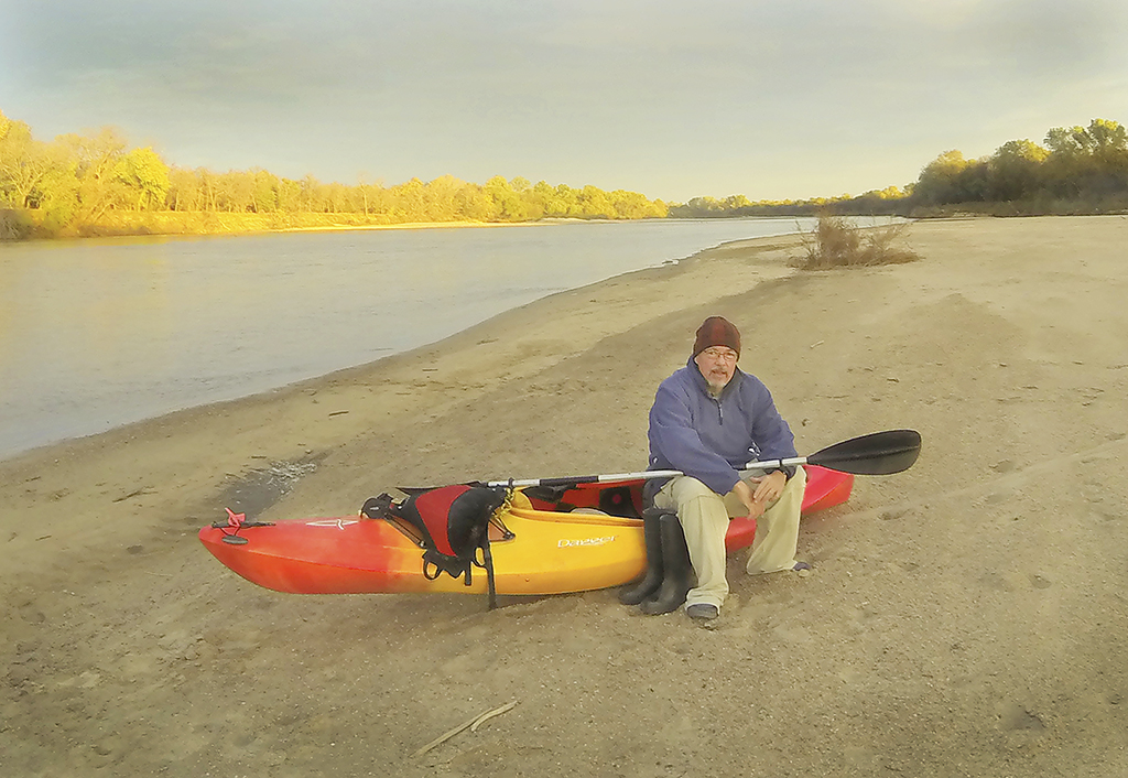 Max McCoy, author and journalism professor at Emporia State University, sits outside the kayak he used to journey down the Arkansas River.