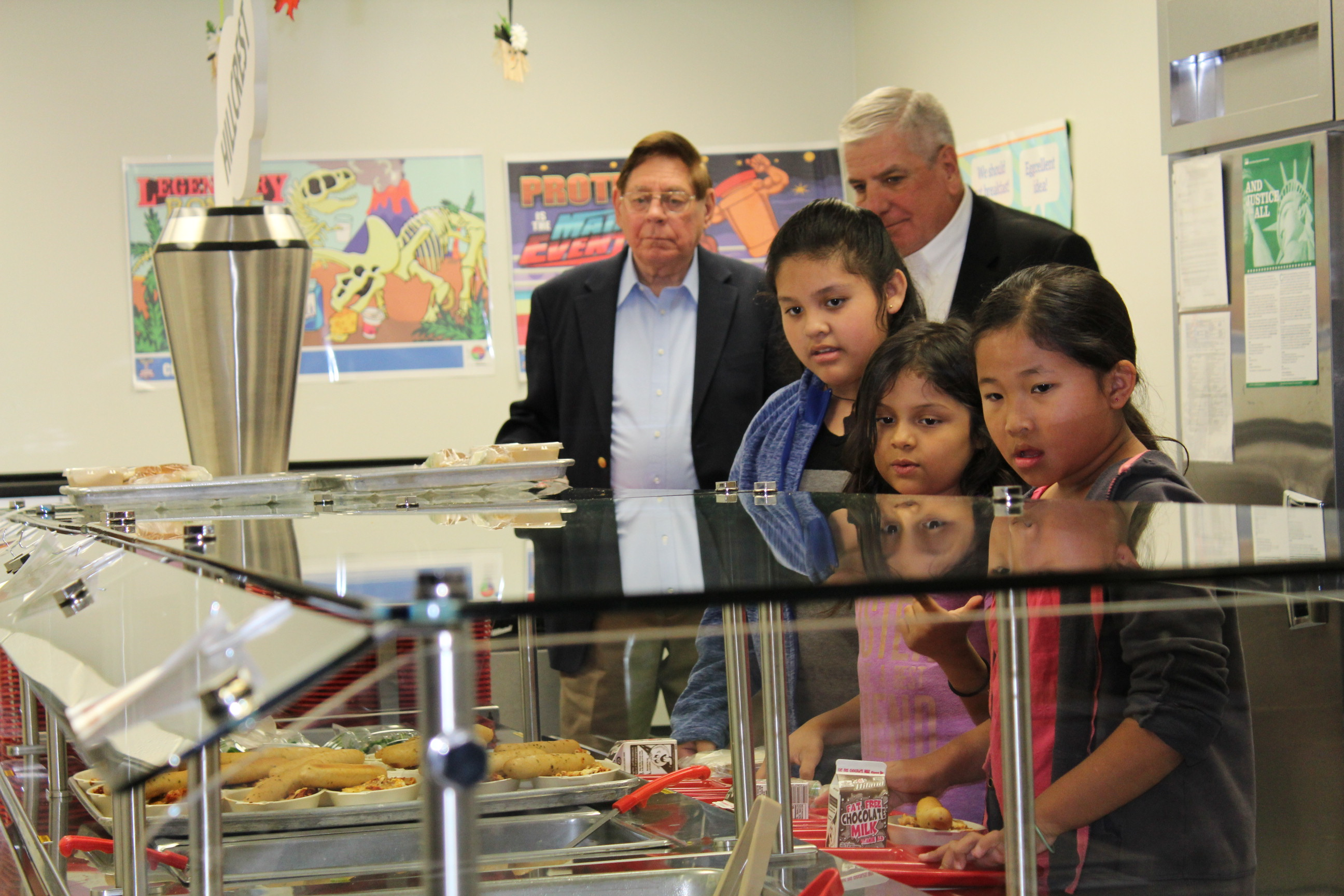 Retired army generals Edward Gerhardt (left) and Daryl McCall get in the lunch line behind students at Hillcrest Elementary School.