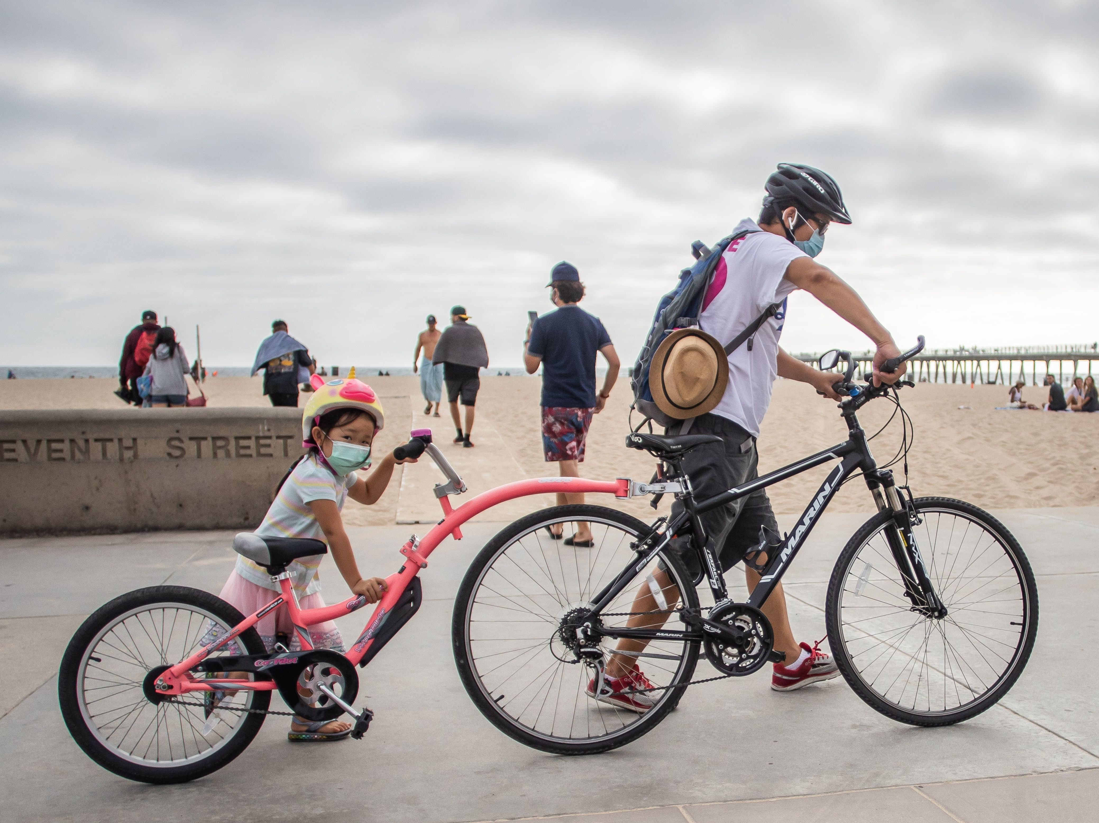 A girl and her father wear facemasks while they push their bikes last summer in Hermosa Beach, Los Angeles. There aren't yet coronavirus vaccines approved in the U.S. for kids under 12 — which means they should keep masking, according to the CDC.