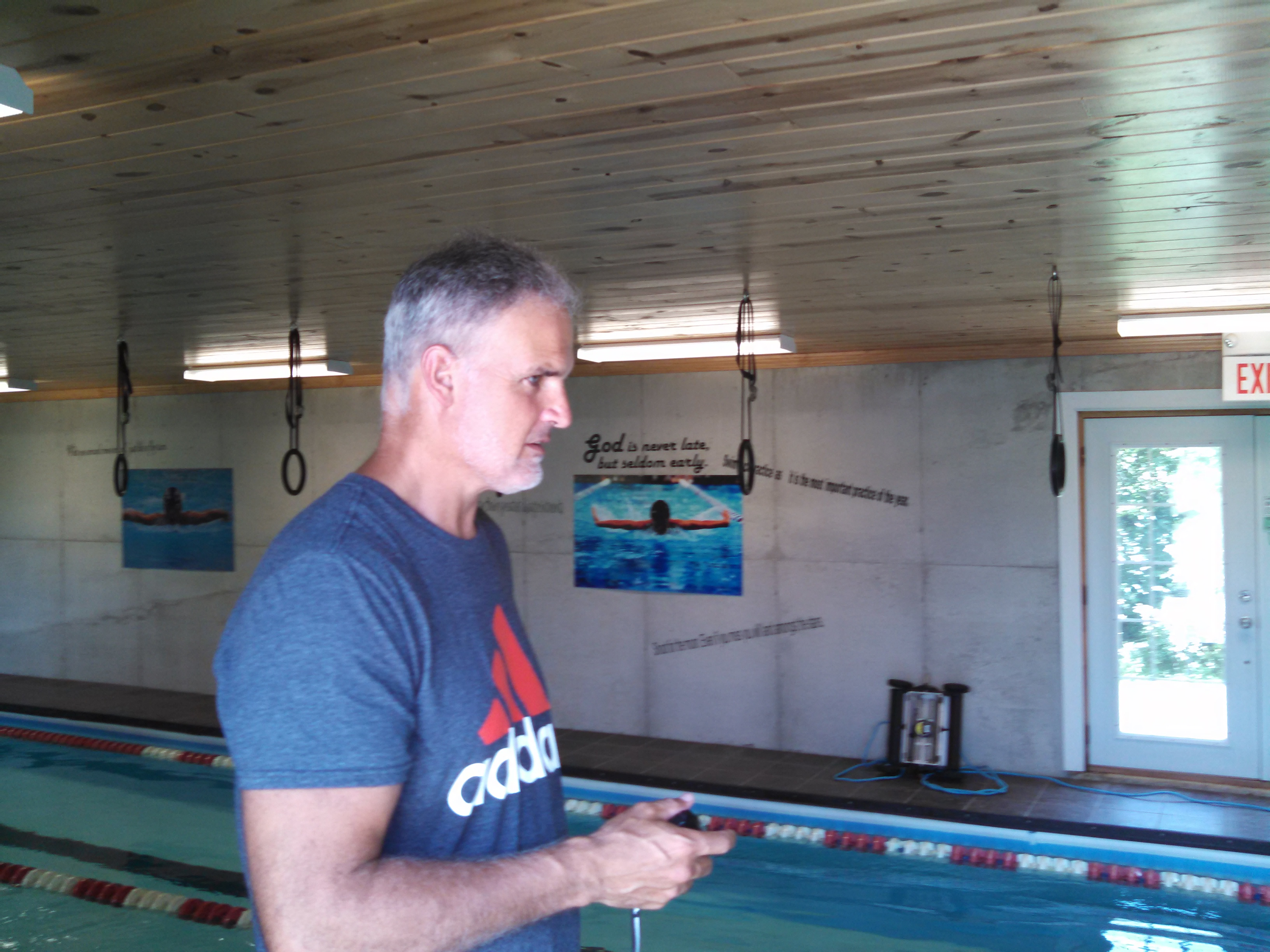 Peter Andrew, Michael's father and trainer, watches his son take laps in the family's pool. (Photo by Ian Echlin)