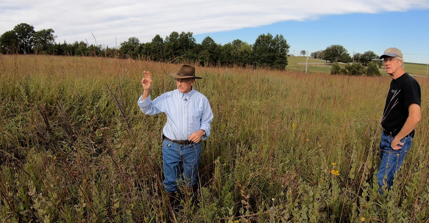Roger Boyd, president of the Douglas County chapter of the Santa Fe Trail Association, speaking with Rex Buchanan, along the Santa Fe Trail near Baldwin City. (Photo by Dave Kendall)