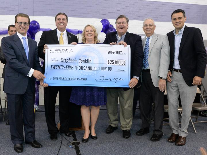 Stephanie Conklin receiving $25,000 check, which comes with winning the Milken Educator Award.  (Photo by Milken Family Foundation)