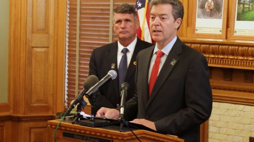 Governor Sam Brownback announcing his request for public input on education funding. Behind him is Kansas State Board of Education Chairman Jim McNiece. (Photo by Stephen Koranda)
