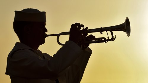 Sailor playing the bugle at sunset. (Photo from Wikimedia Commons)