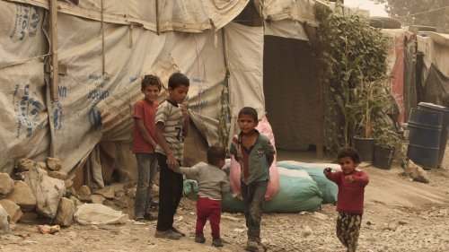 Children stand outside tents during a sandstorm in a refugee camp in Lebanon.  (AP Photo by Bilal Hussein, from npr.org)