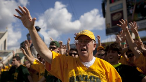 Ken Starr cheers with Baylor University students before a 2012 game against the University of Kansas Jayhawks in Waco, Texas.