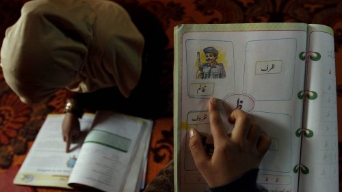 A student reads inside her home in Srinagar, India, as her sister points to a sketch resembling a male police officer in a first-grade textbook