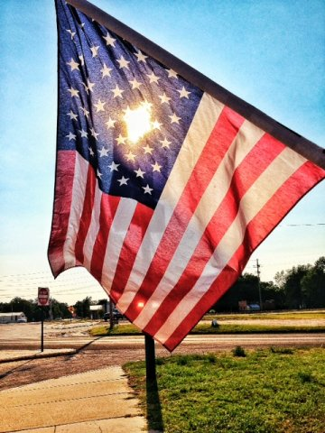 An American flag hangs in downtown Arlington, Kansas. (Photo by J. Schafer)
