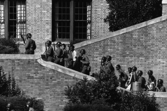Soldiers from the 101st Airborne Division escort the Little Rock Nine students into the all-white Central High School in Little Rock, Ark, 1957. (Photo Courtesy of National Archives)