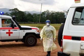 A health worker, wearing a personal protective equipment, returns to her ambulance on November 11, 2014 after tranporting a patient to the Hastings treatment center in Hastings, outside Freetown, the only run exclusively by locals.