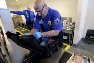 A TSA agent checks a bag at a security checkpoint area at Midway International Airport last month. The new federal government guidelines on racial and religious profiling won't apply to the TSA.