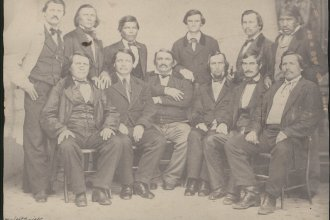 This formal portrait shows a group of Delaware Indians. The group have been identified from left to right by their respected rows. FRONT ROW: James Ketchum, James Connor, John Connor, Charles Journeycake, Isaac Journeycake, John Sarcoxie, Sr. BACK ROW: James McDainel, (Cherokee), Black Beaver, Henry Tiblow, John G. Pratt, Charles Armstrong, John Young. Date: Between 1860 and 1865 (Photo via Kansas Historical Society/kansasmemory.org)