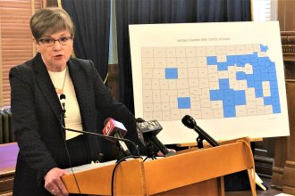 Kansas Gov. Laura Kelly explains her decision to mandate a statewide stay-at-home order on Saturday. The map shows the counties that have confirmed coronavirus cases. (Photo by Jim McLean, Kansas News Service)