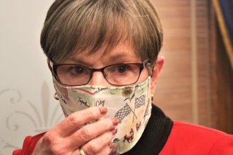 Kansas Governor Laura Kelly puts on a mask after a news conference on June 22. (Photo by Jim McLean, Kansas News Service)