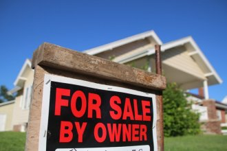 """A """"for sale"""" sign posted outside a home in Hays. (Photo by David Condos, Kansas News Service)"""